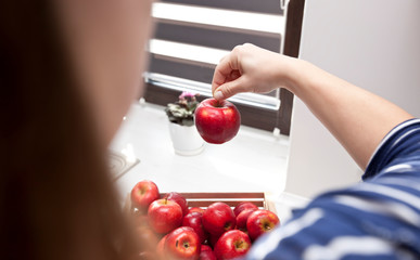 The woman is taking red apple from basket with fruits