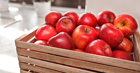 A lot of juicy red apples in the wooden box on the wooden table in the kitchen