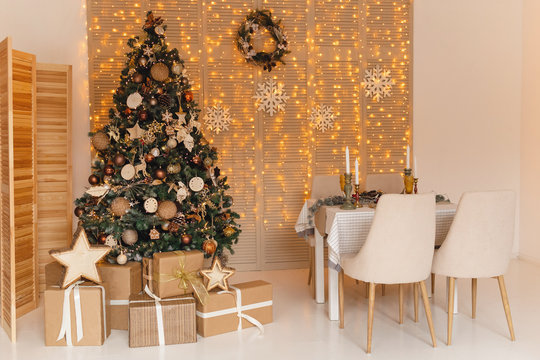 Christmas interior with big gold christmas tree and served table. celebration concept. Merry christmas concept.