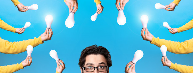Wall Mural - Head of young man with bulbs lights over blue background, panoramic image, concept a lot of ideas