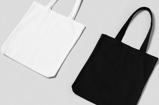 White and black tote bags mockup on a grey background.