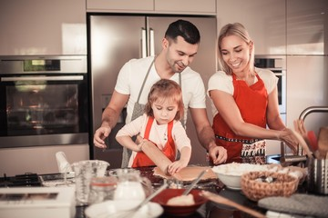 Tuinposter Koken Beautiful family bake christmas cookies. Family cooks in the kitchen. Holidays. Christmas. New Year. Cozy.