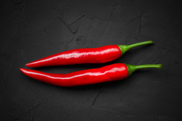 Canvas Prints Hot chili peppers Red ripe chili peppers on a black background, top view