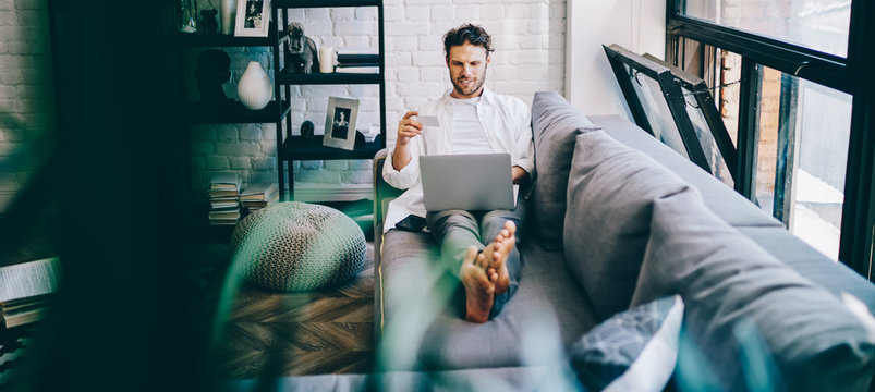 Cheerful hipster guy lying on sofa in modern designed living room making online shopping via laptop computer and wifi, man holding credit card paying for purchases in web store rest at home.
