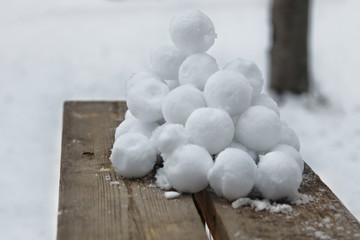 A slide of stuck snowballs on a wooden bench in the yard.