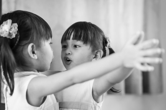 Adorable asian little girl is looking herself in the mirror and talk something with happiness moment.