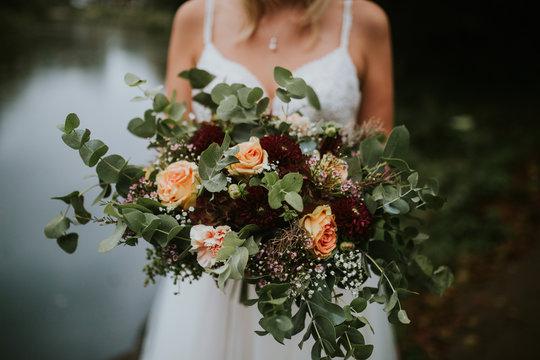 bride holding beautiful wild boho wedding bouquet with wild flowers