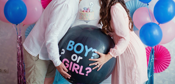 """man and woman holding black balloon with """"boy or girl?"""" on gender reveal party"""