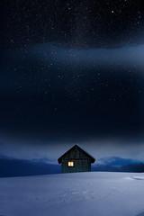 Blockhaus mit Leuchtendem Fenster im Winter bei Dämmerung