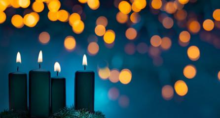 Vier brennende Weihnachtskerzen auf einem Adventskranz