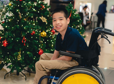 Disabled child on wheelchair with Blurry lights and decorations on the Christmas tree, Special children's lifestyle, Life in the education age of special need kids, Happy disability kid concept.