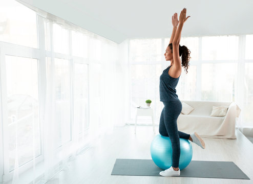 Beautiful sporty girl doing exercises with fit ball at home