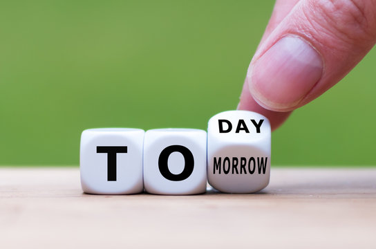 """Hand turns a dice and changes the word """"tomorrow"""" to """"today"""", or vice versa."""