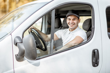 Portrait of a cheerful delivery driver in uniform looking out the window of the white cargo van vahicle, delivering goods by car