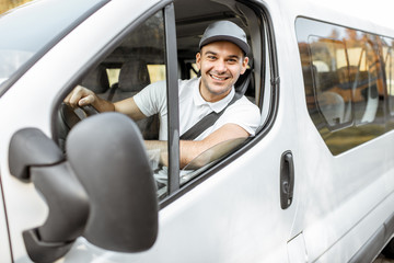 Portrait of a cheerful delivery driver in uniform looking out the window of the white cargo van...