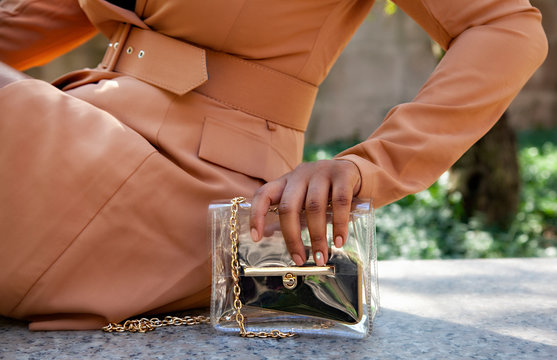 close up shop of a African american black woman hands holding a clear hand bag by a water fountain in Chicago.  she's wearing a fashionable brown trench coat.