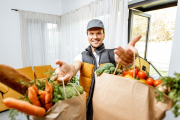 Portrait of a cheerful courier in uniform delivering fresh groceries home, holding paper bags full of food in front of the camera indoors