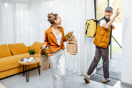 Courier delivering fresh groceries home for a young client, happy woman standing with purchases with delivery man leaving home
