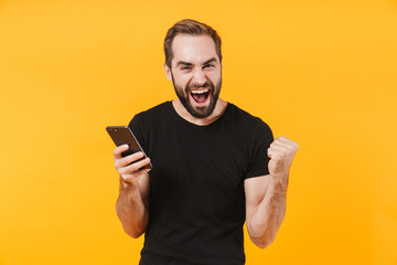 Image of cheerful man wearing t-shirt rejoicing and holding smartphone Fotobehang