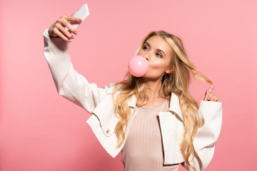 blonde young woman with pink bubble gum in mouth taking selfie on pink