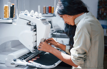 Beautiful female worker is in the sewing factory by the machine Fotomurales