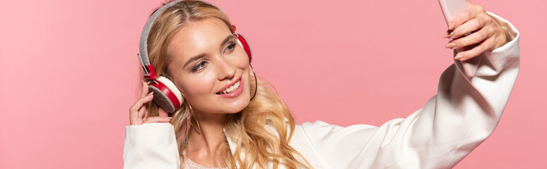 panoramic shot of beautiful blonde woman with headphones taking selfie on smartphone isolated on pink
