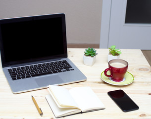 Desktop wood table with laptop, smart phone, notebook and cup of coffee
