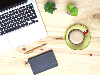 Top view of desktop wood table with laptop, notebook and cup of coffee