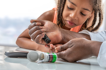 Concept children diabetes children with glucometer learning to check blood sugar level at home. Learn to use a glucometer