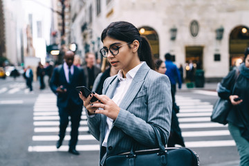 Hispanic female entrepreneur dressed in formal jacket making online communication on website typing sms answer via smartphone gadget, intelligent young woman using 4g wireless on cellphone device