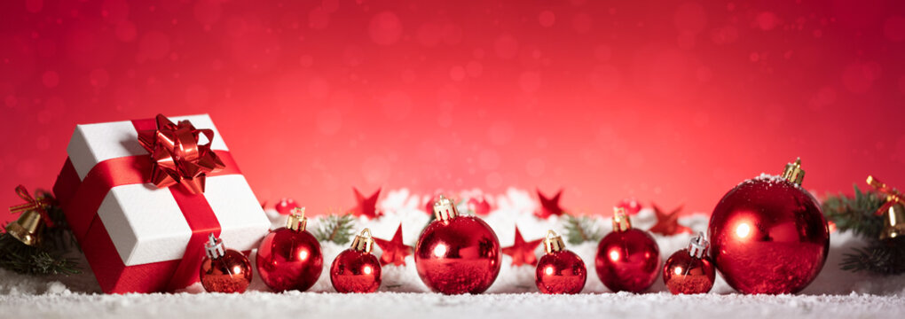 Panoramic image of gift box and red christmas balls on snow
