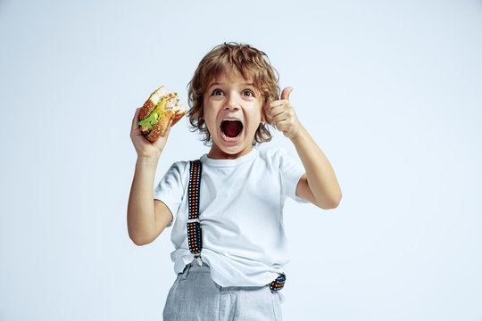 Pretty young curly boy in casual clothes on white studio background. Eating burger. Caucasian male preschooler with bright facial emotions. Childhood, expression, fun, fast food. Showing thumb up.