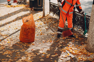 Janitor cleaner sweeping autumn leaves on the street