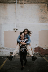 Young man giving beautiful woman a piggyback ride