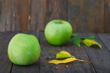 Delicious green apple with leaves and seeds on wooden background. Healthy Granny Smith apples.