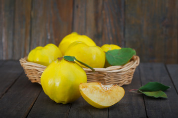 Delicious yellow quinces in a abasket with leaves on wooden background. Healthy apple quince, one cut.