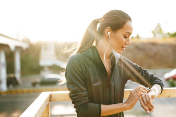 Image of young focused woman using earphones and smartwatch Wall mural