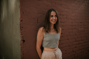 Young pretty woman in front of brown wall smiling