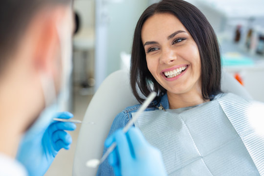 smiling woman in dental chair with doctor holding dental mirror