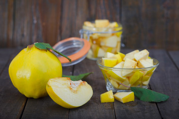 Yellow quince compote in a jar and a bowl on wooden background. Compote - sweet and healthy fruit dessert.