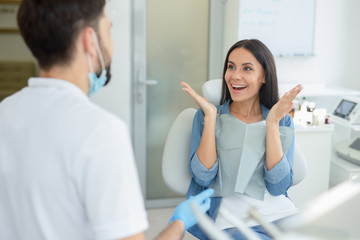 woman gesturing near dentist talking to her in clinic
