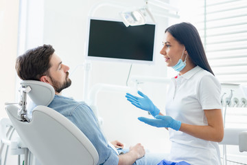 side view of female dentist advicing and gesturing to client sitting in dental chair