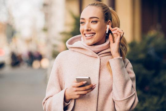 Millennial woman enjoying music in airpods, walking in city