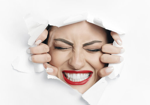 Young beautiful woman is struggling to break through a white material wall