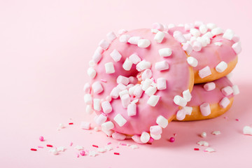 Wall Mural - Pink glazed donuts with marshmallows on pink background close-up