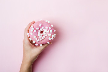 Wall Mural - Female hand holding pink donut with marshmallows over pink background
