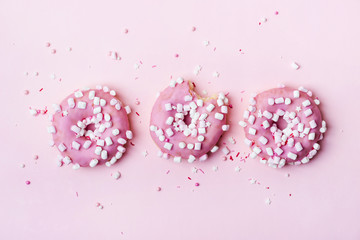 Fototapete - Creative layout made of pink donuts with marshmallows and sprinkled. Food concept