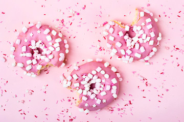 Wall Mural - Creative layout made of pink bitten donuts with marshmallows. Food concept