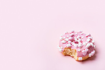 Wall Mural - Bitten Pink donut with marshmallows and sprinkled. Minimal concept