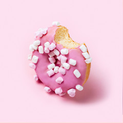 Fototapete - Bitten pink icing donut with marshmallows on pink background. Minimal concept in monochrome pastel colors